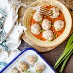 Delicious Chicken Cauliflower Meatballs served in a big cute bowl with a forn on top and a white tray with more meatballs on a wooden board