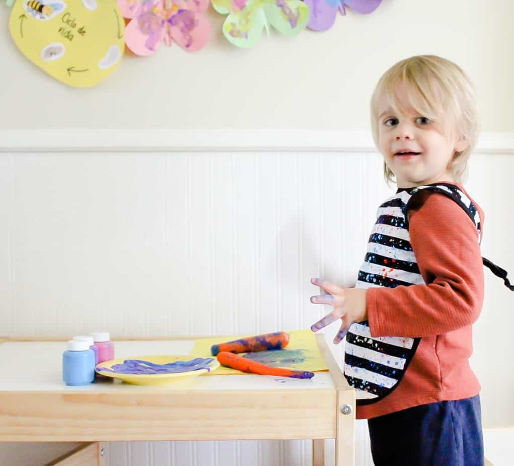 little boy painting with carrots