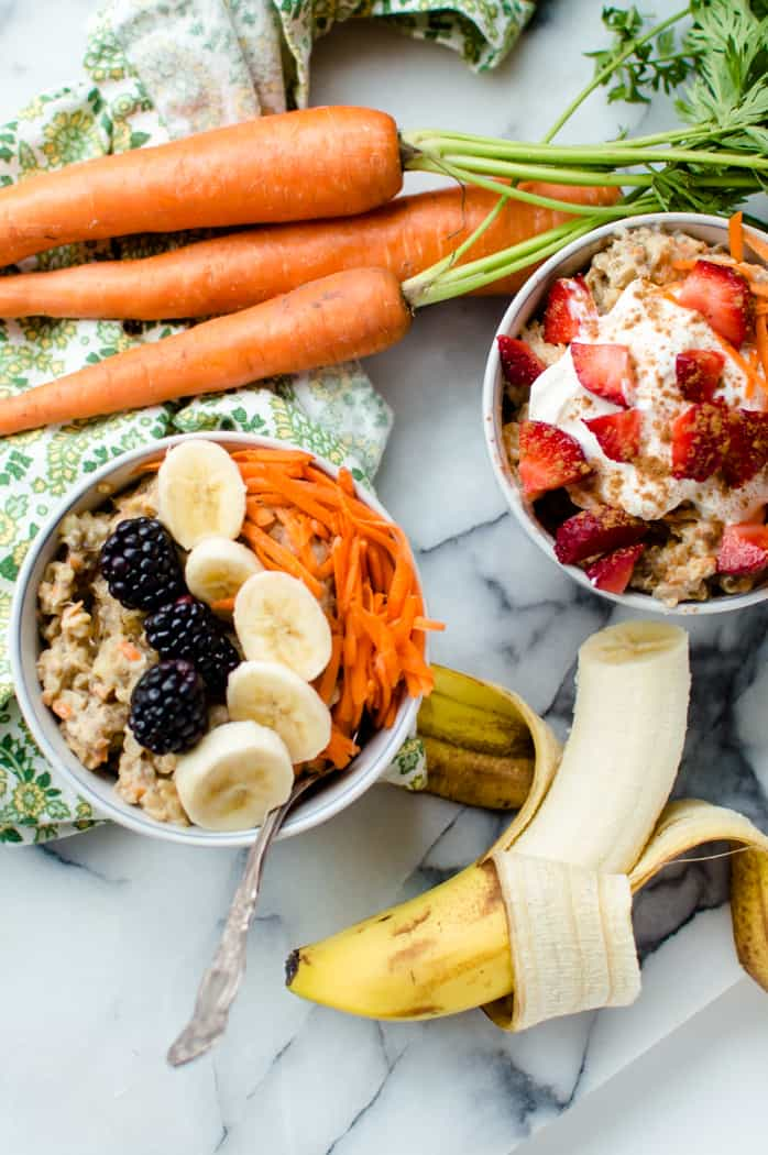 Two bowls of oatmeal with bananas and carrots around them.