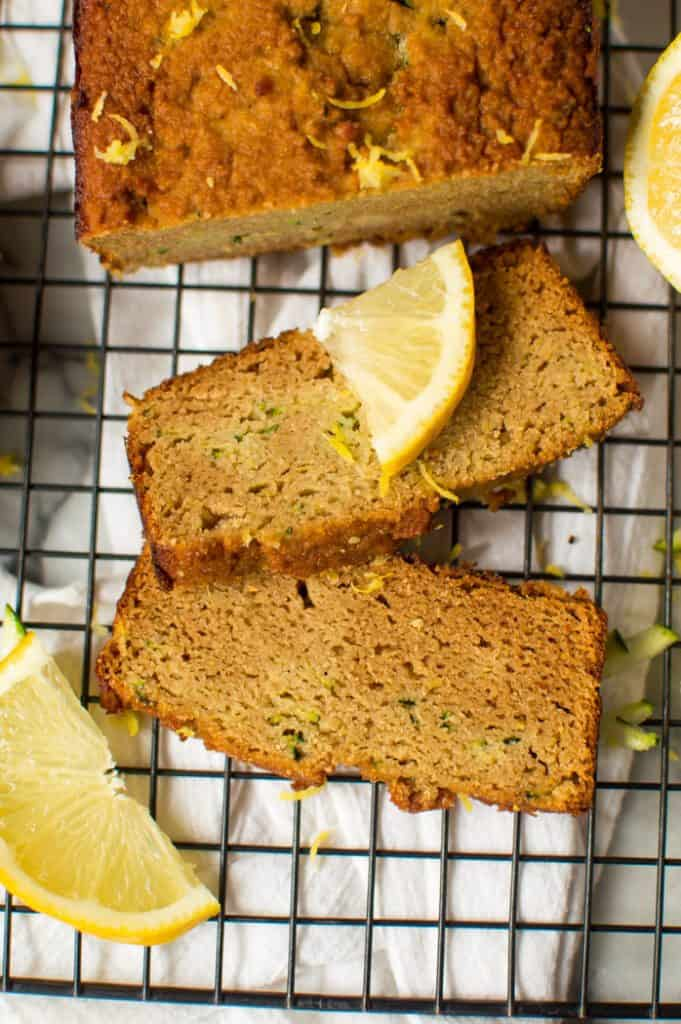 A loaf of lemon zucchini bread on a cooling rack, cut into a slices