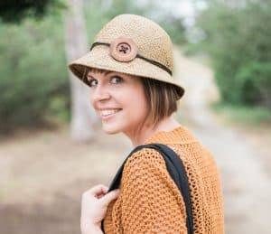 blond woman with a hat looking over her shoulder and smiling.