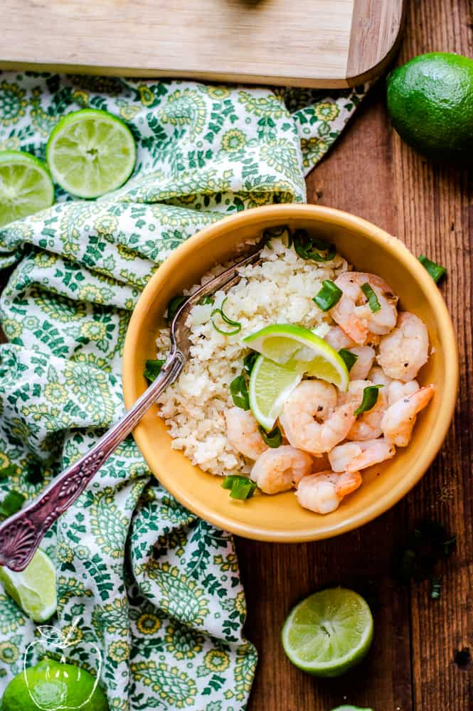 Overhead on a bowl full of the delicious Zesty Lime Shrimp with Simple Cauliflower Rice and pieces of lime on the wooden table