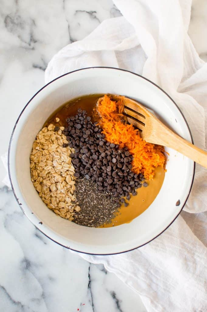 The ingredients for carrot peanut butter balls before being mixed together. They are displayed in a white bowl  on top of a white marble surface with a wooden spoon resting on the edge of the bowl and a white tea cloth
