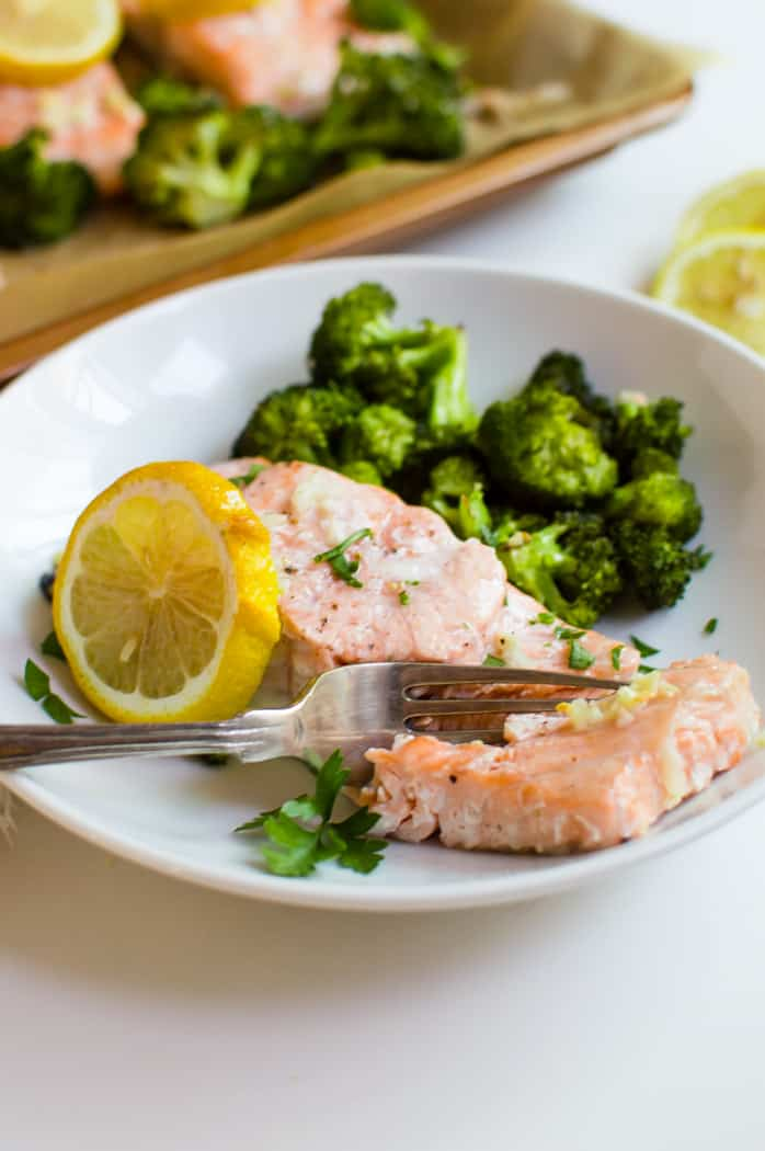 This One-Sheet Roasted Garlic Salmon & Broccoli is easy, quick, and full of flavor! A complete & delicious dinner that is Whole30, gluten free, and dairy free made entirely on one sheet pan….could it get any better?
