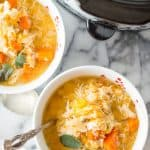 Slow Cooker Chicken Butternut Squash Stew ready and served in two big white bowls next to the pan with more delicious soup inside