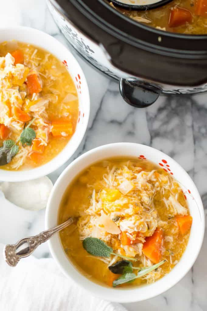Slow Cooker Chicken Butternut Squash Stew ready and served in two big white bowls next to the pan with more delicious soup inside.