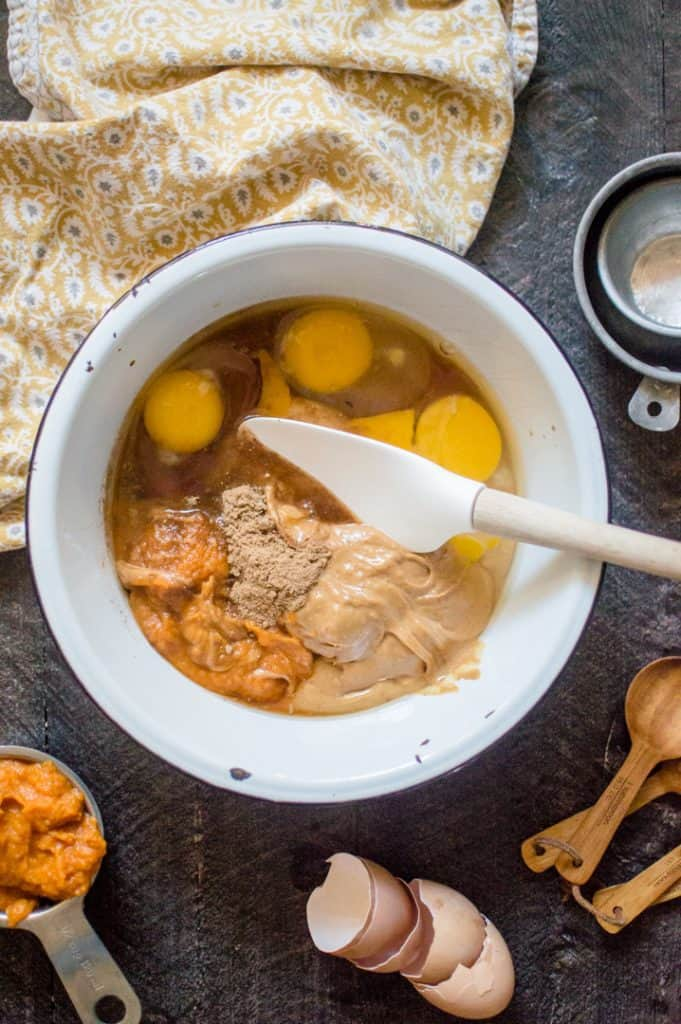 Mixing all ingredients necessary to make Peanut Butter Muffins in a big white bowl on a dark grey surface with a yellow towel next to the bowl.