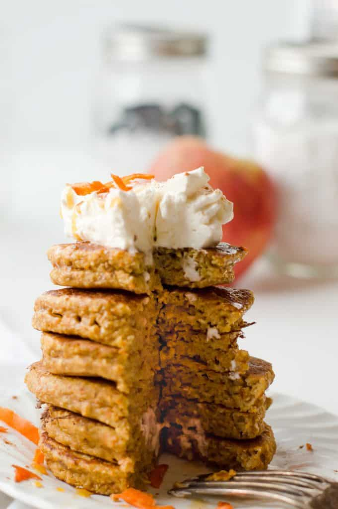 a stack of pancakes topped with whipped cream