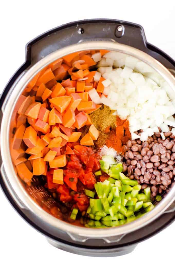 Slow Cooker Black Bean & Sweet Potato Chili is an easy, healthy and delicious dinner!  This slow cooker soup is full of warm cozy flavors and family-friendly. Gluten free + vegan.