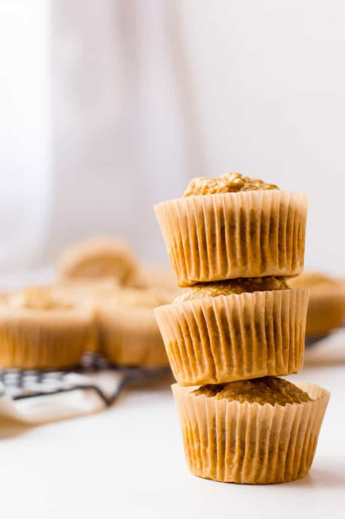 A tall tower of three carrot pumpkin muffins - one of the 15 healthy muffin recipes for kids