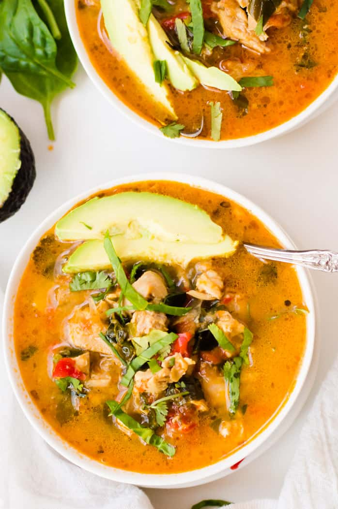 Overhead on a big bowl of the delicious Mexican Slow Cooker Chicken Stew with avocado, greens and other healthy ingredients on top