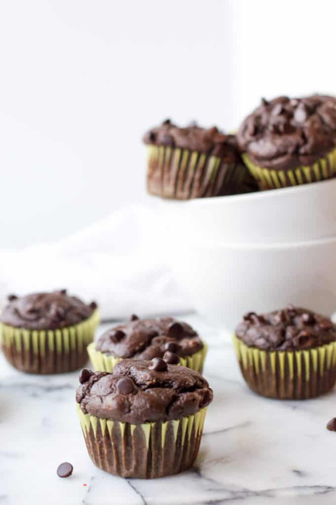 chocolate butternut squash muffins on a white table with muffins in a bowl in the background