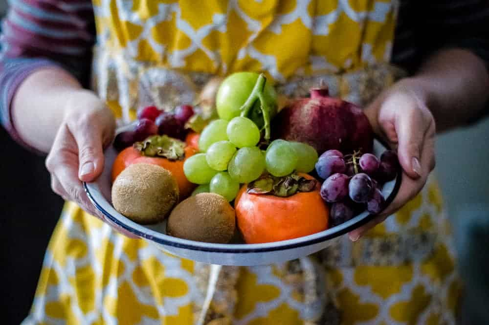 fruit in a bowl with a woman holding it
