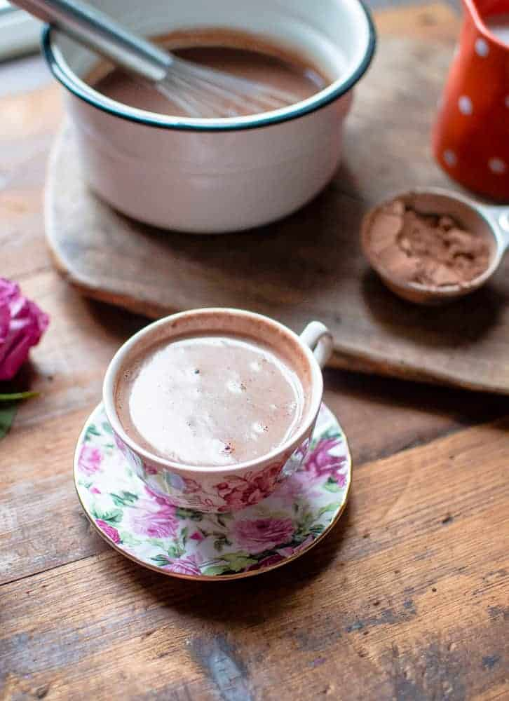 A cup of hot chocolate with the pot and ingredients blurred in the background, looking absolutely warming and delicious