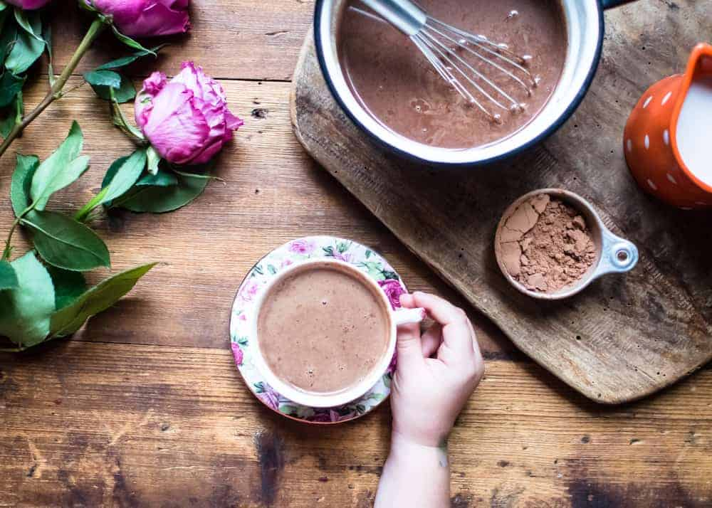 Cup of hot chocolate with a child's hand holding it above the vintage wooden table