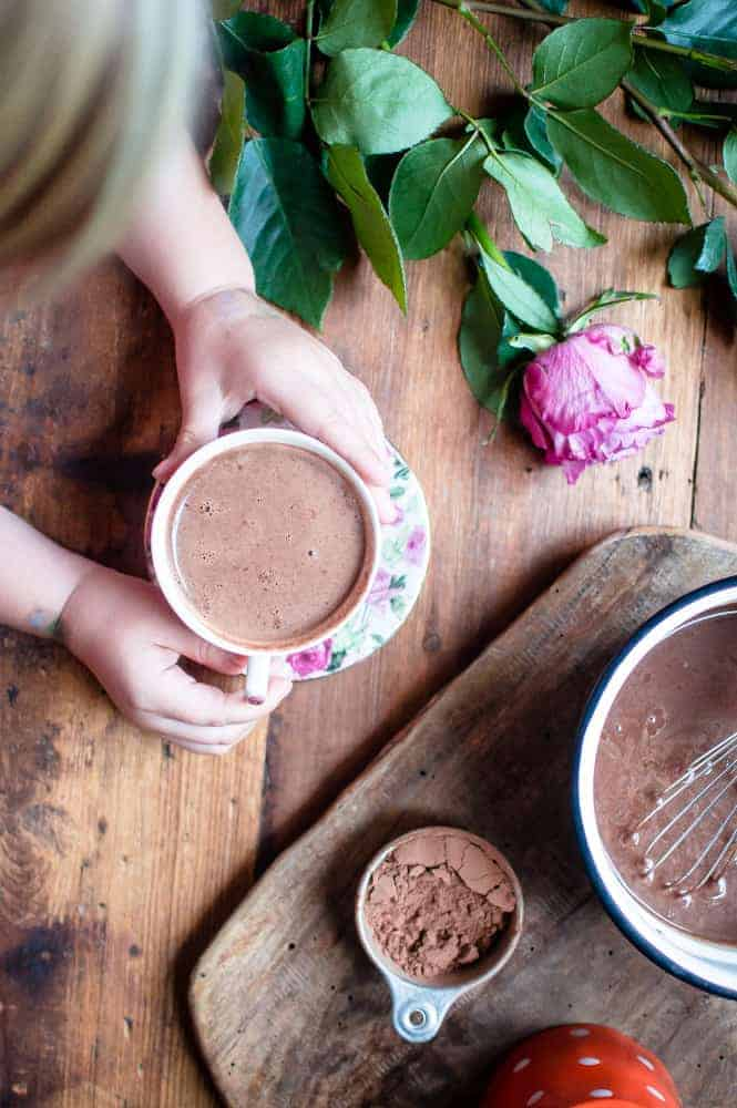 Kid hands holding a big cup of the best Homemade Hot Chocolate served with a beautiful rose on a wooden table