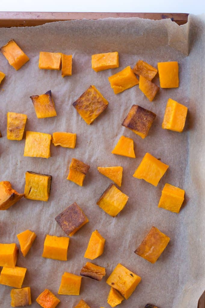 cubed roasted butternut squash on a baking sheet