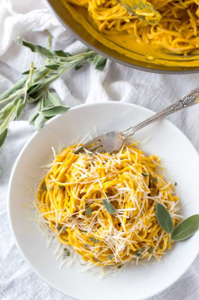 A bowl of pumpkin pasta sauce with parm cheese and sage on top
