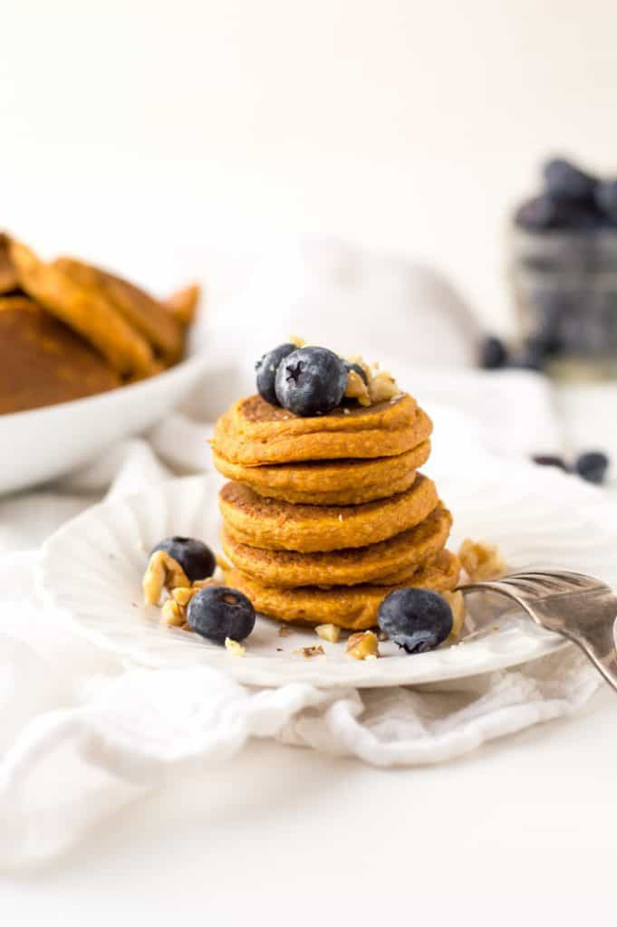 A big stack of healthy sweet potato pancakes topped with blueberries and more pancakes blurred in the background.
