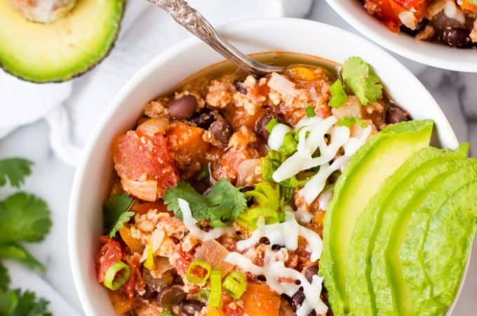 bowl of chili with avocado and cheese on top