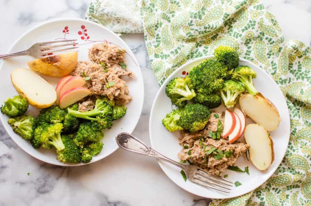 two plates of pulled pork with roasted broccoli and potatoes