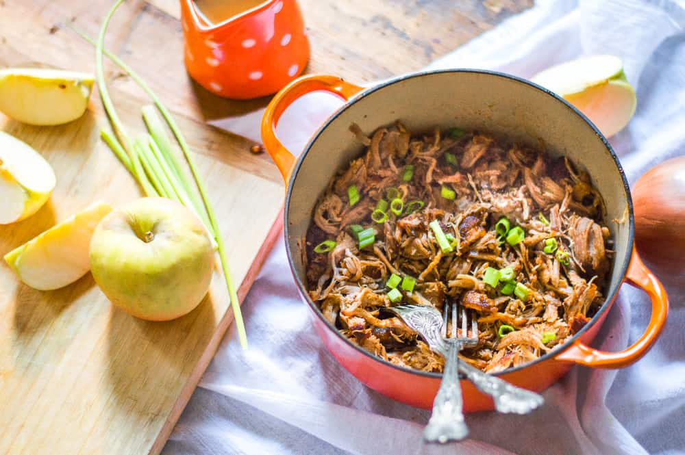 slow cooker pulled pork in a pot with apples and green onions around it