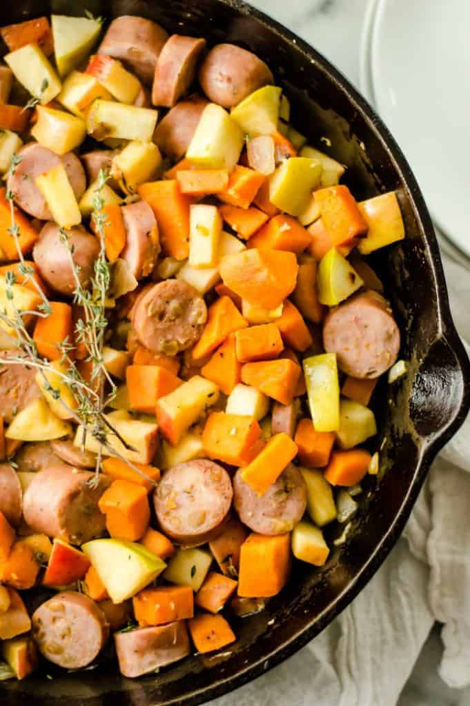 A close  up of sweet potato apple sausage skillet in the pan garnished with fresh thyme