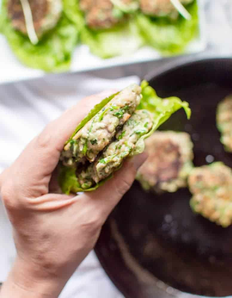 veggie-loaded chicken burgers in a lettuce wrap in someone's hand