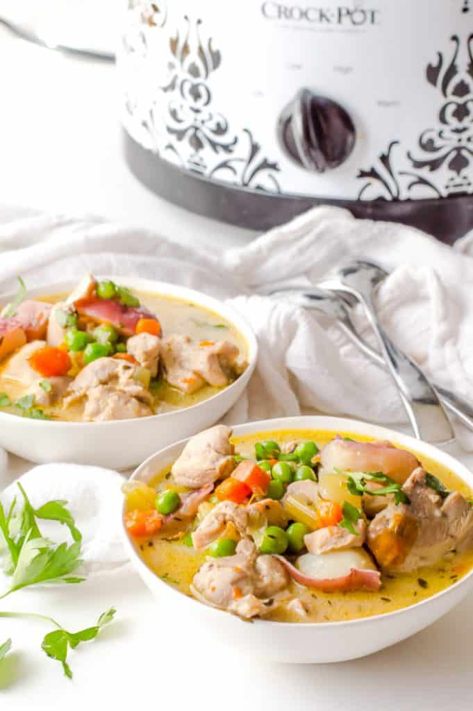 Two bowls of slow cooker creamy vegetable chicken stew on the table with spoons nearby and crockpot in the background.