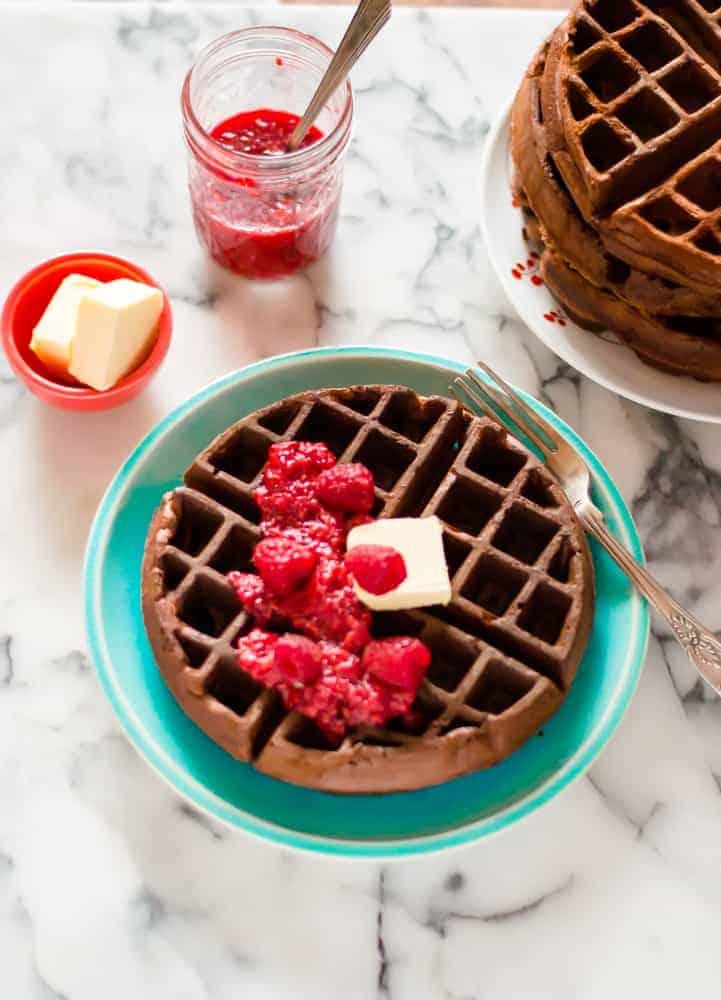 veggie-loaded chocolate waffles on a plate with raspberry sauce