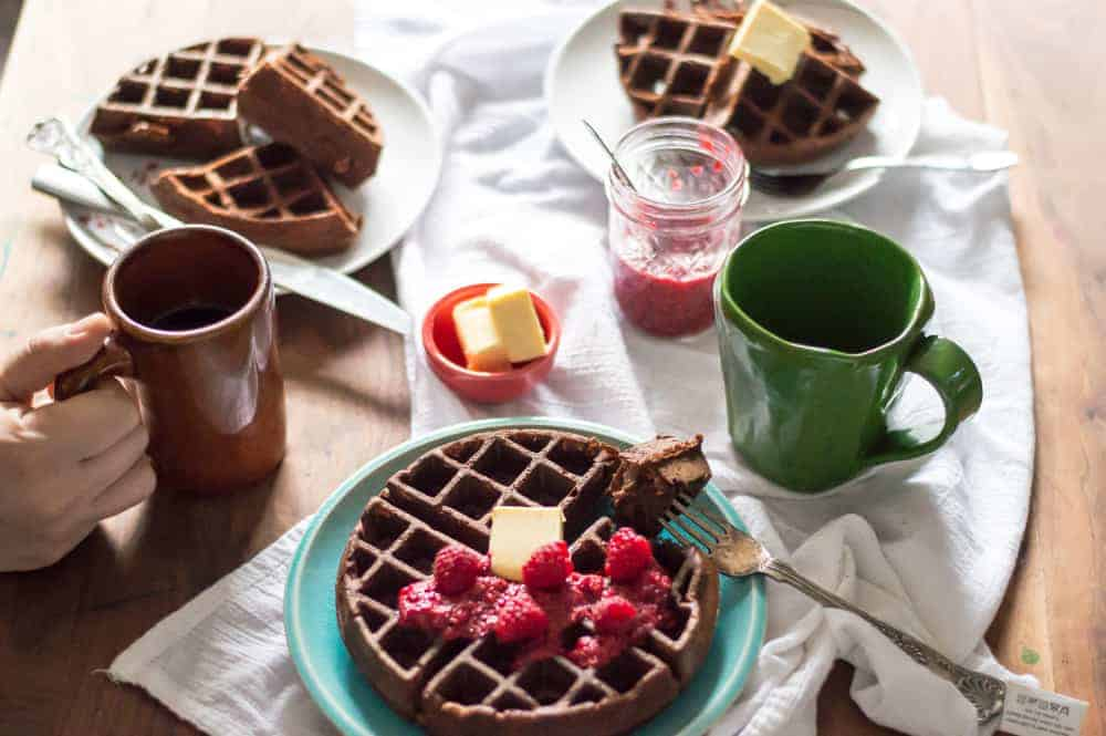 veggie-loaded chocolate waffles on a breakfast tables with coffee and butter