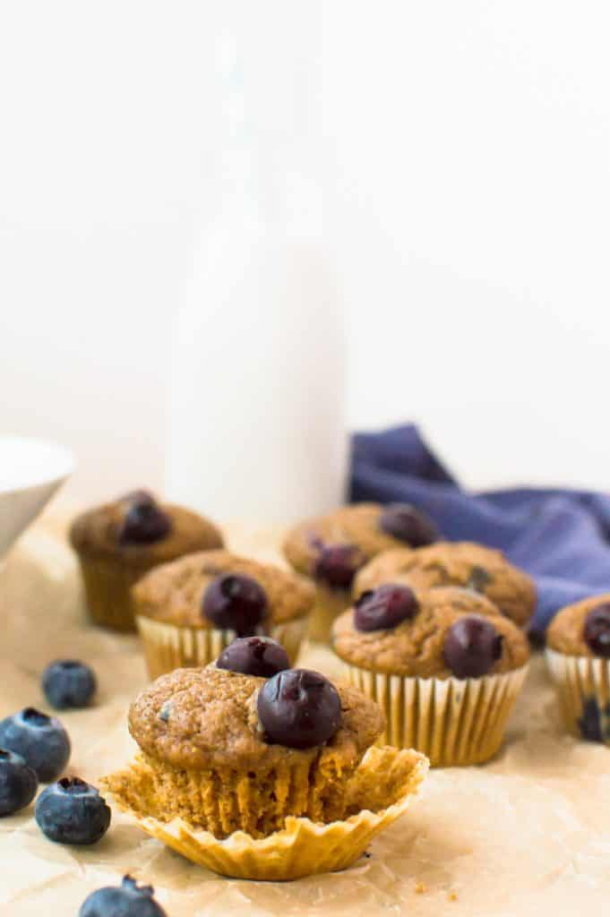 Mini wholewheat blueberry muffins on a table with fresh blueberries. One muffin is out of its wrapper.
