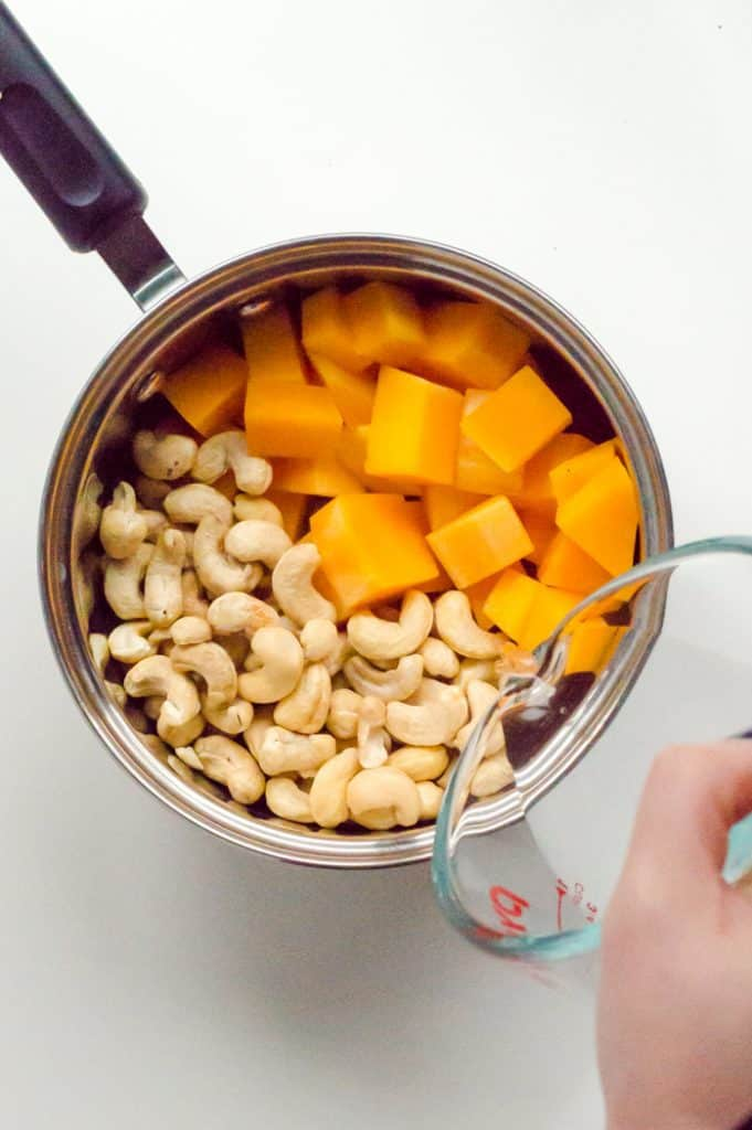 A pot of butternut squash and cashews with water being poured on it