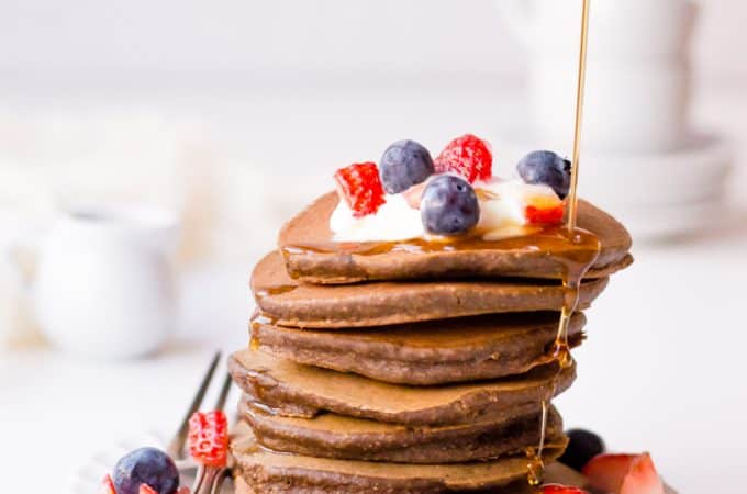 Veggie-packed chocolate pancakes served in a tower with many different berries on top and honey being poured from the top