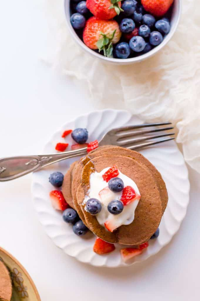 Top view of veggie-loaded chocolate pancakes with yogurt and berries on top