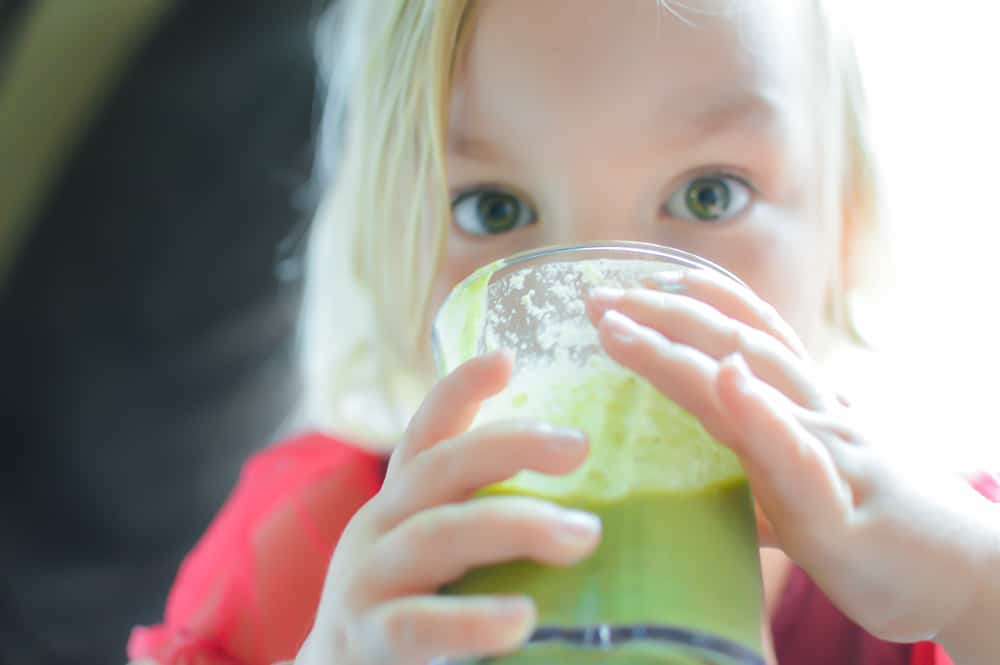 A little girl drinking a green smoothie out of a glass and looking at the camera