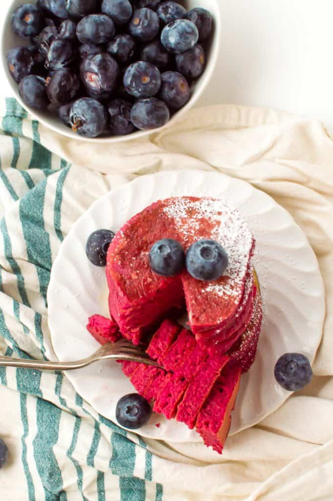 A stack of beet pancakes with blueberries and a slice taken out of them.