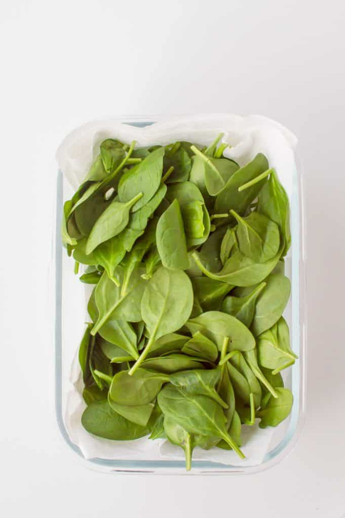 A container of spinach with a paper towel.
