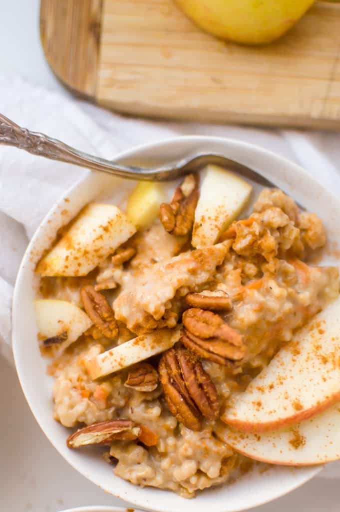 A bowl of slow cooker steel cut oatmeal with apples, cinnamon and nuts on top.