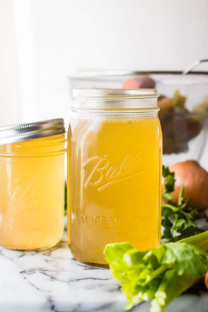 Homemade vegetable broth cooling in a mason jar with the ingredients in the background.