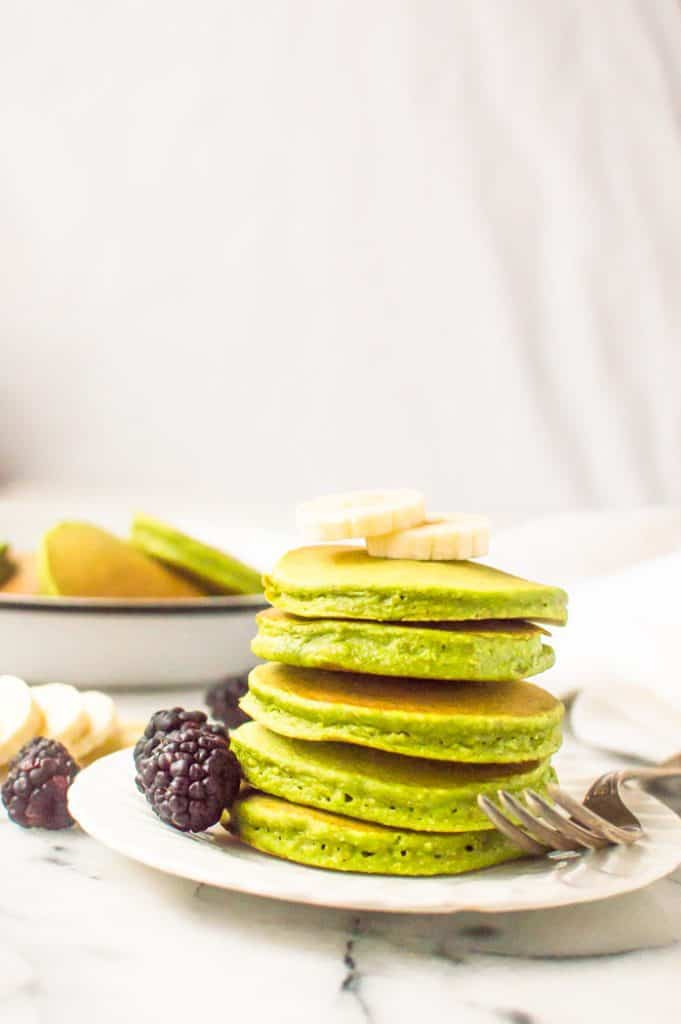 a stack of bananas spinach pancakes topped with bananas