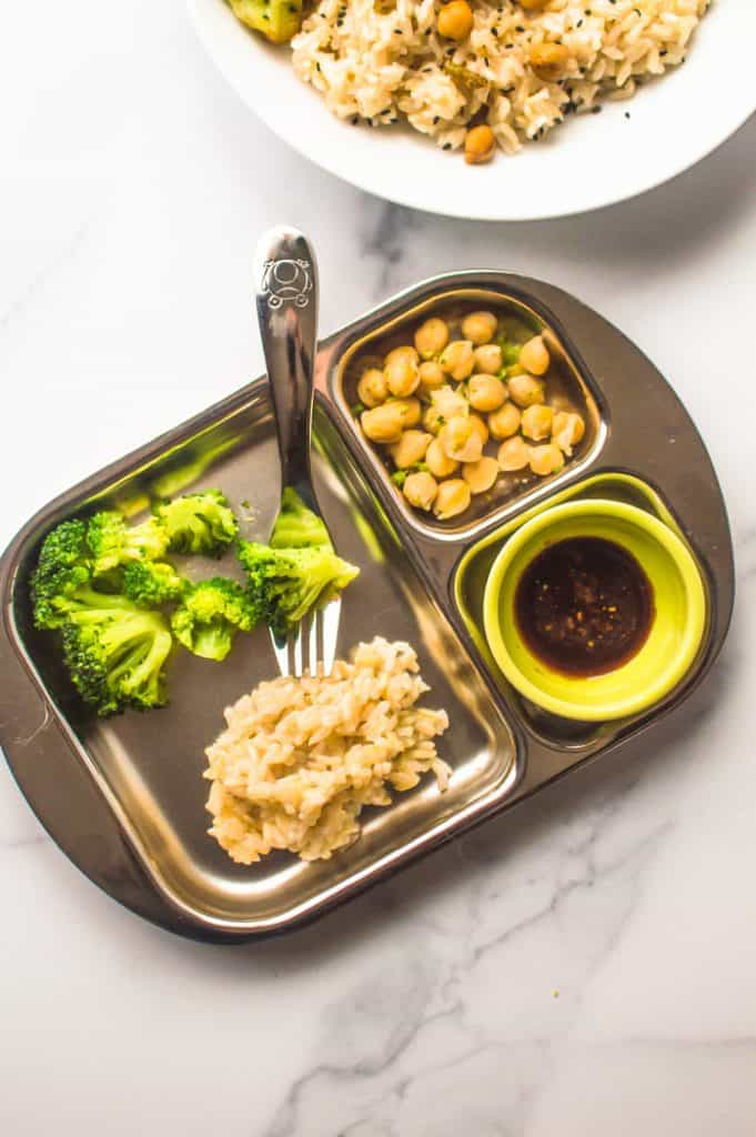 Broccoli chickpea stir fry deconstructed on a child's sectioned off plate as an example on how to serve it to young children.