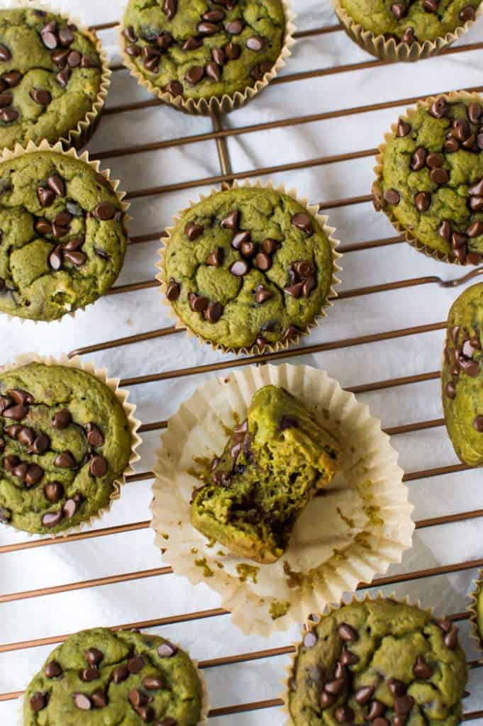 Kid-friendly vegan spinach muffins cooling on rack, with one muffin missing a bite.