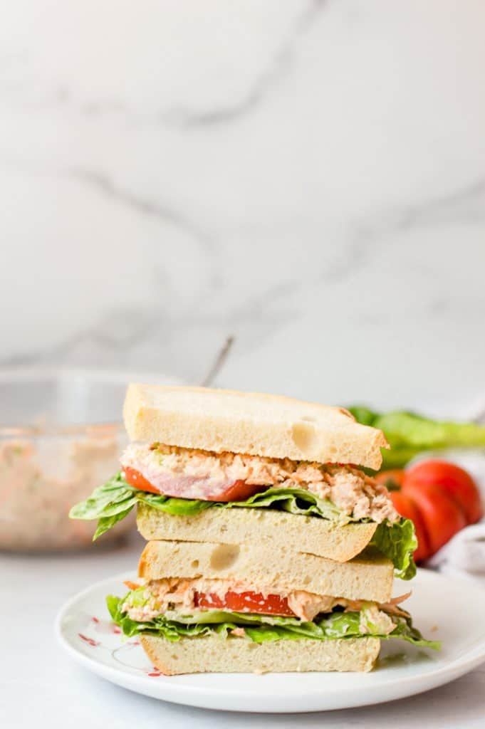 Healthy Tuna salad on a sandwich with lettuce and sandwich ingredients in the background.