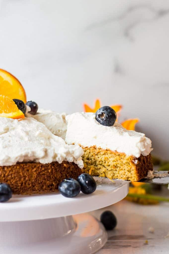 The finished oatmeal carrot cake topped with whipped cream and blue berries. A slice is being removed from the cake.