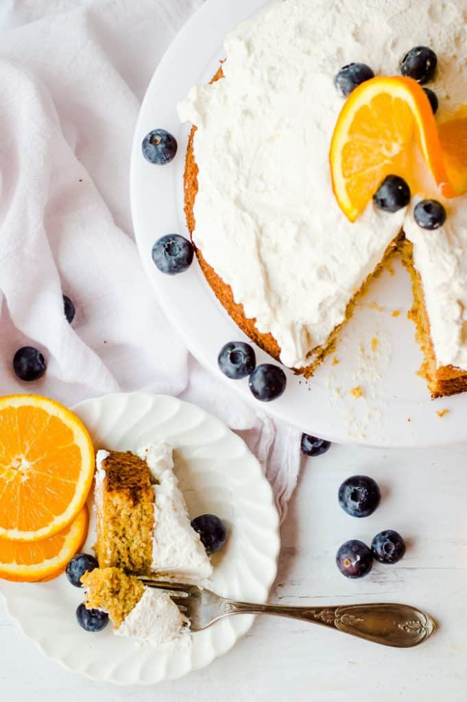 An overhead shot of oatmeal carrot cake topped with whipped cream and decorated with slice oranges and blueberries. A slice is cut from the cake and is on a plate next to the cake with a fork removing a bite.
