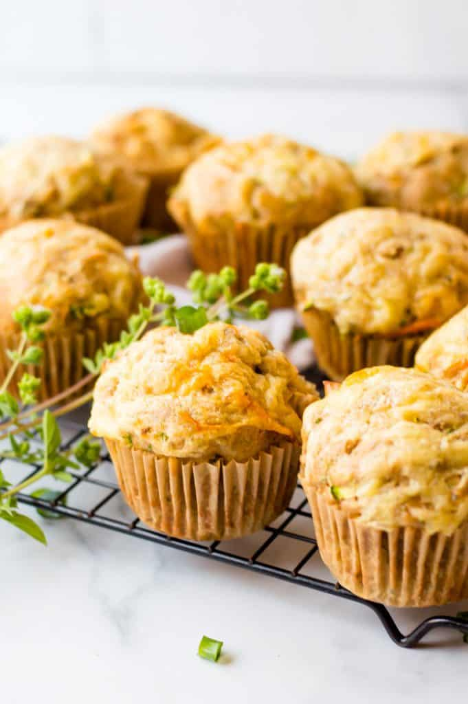 A side view of savory vegetable muffins on a cooling rack and a sprig of fresh thyme next to them.