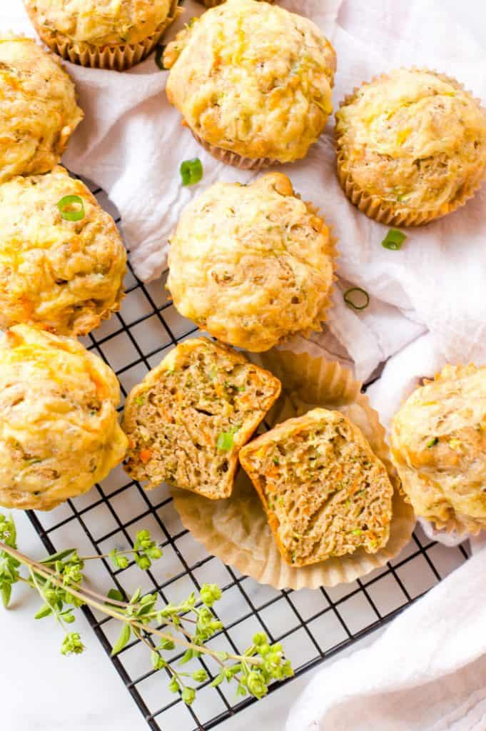 Savory Vegetable Muffins on a cooling rack with a white tea cloth. One muffin is cut open to show the texture of a cooked muffin and there are chopped green onions sprinkled around and fresh thyme next to the muffins.