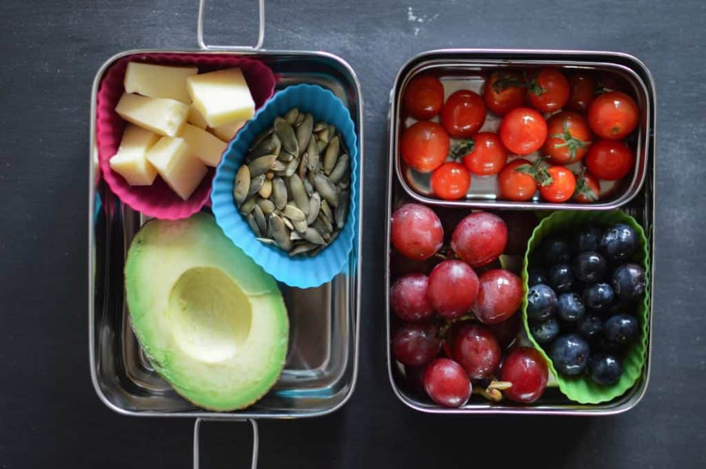 A stainless-steel lunch container with 1/2 an avocado, cheese chunks, seeds, tomatoes, grapes and blueberries.