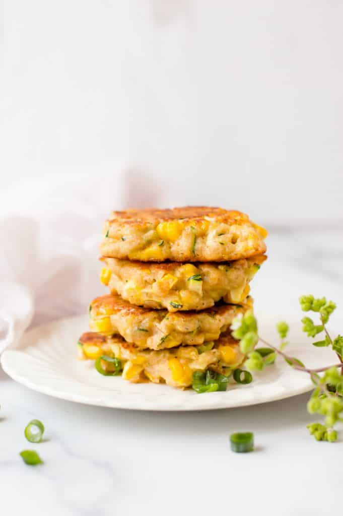 4 zucchini and corn fritters stack on a white plate with sliced green onions scattered around and a spring of fresh thyme next to the plate.